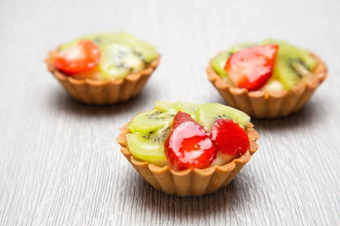 close up photography of three kiwi topped tarts