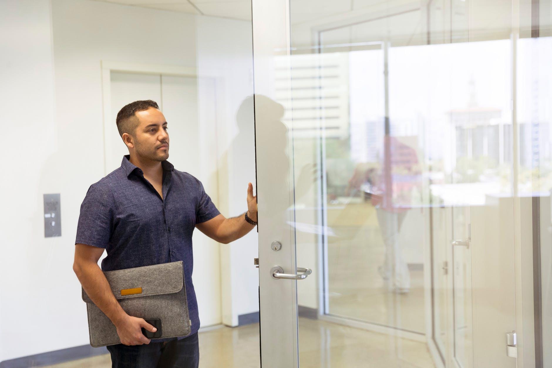 man standing next to glass door