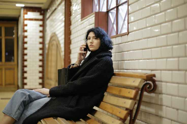woman in black coat sitting on brown wooden bench