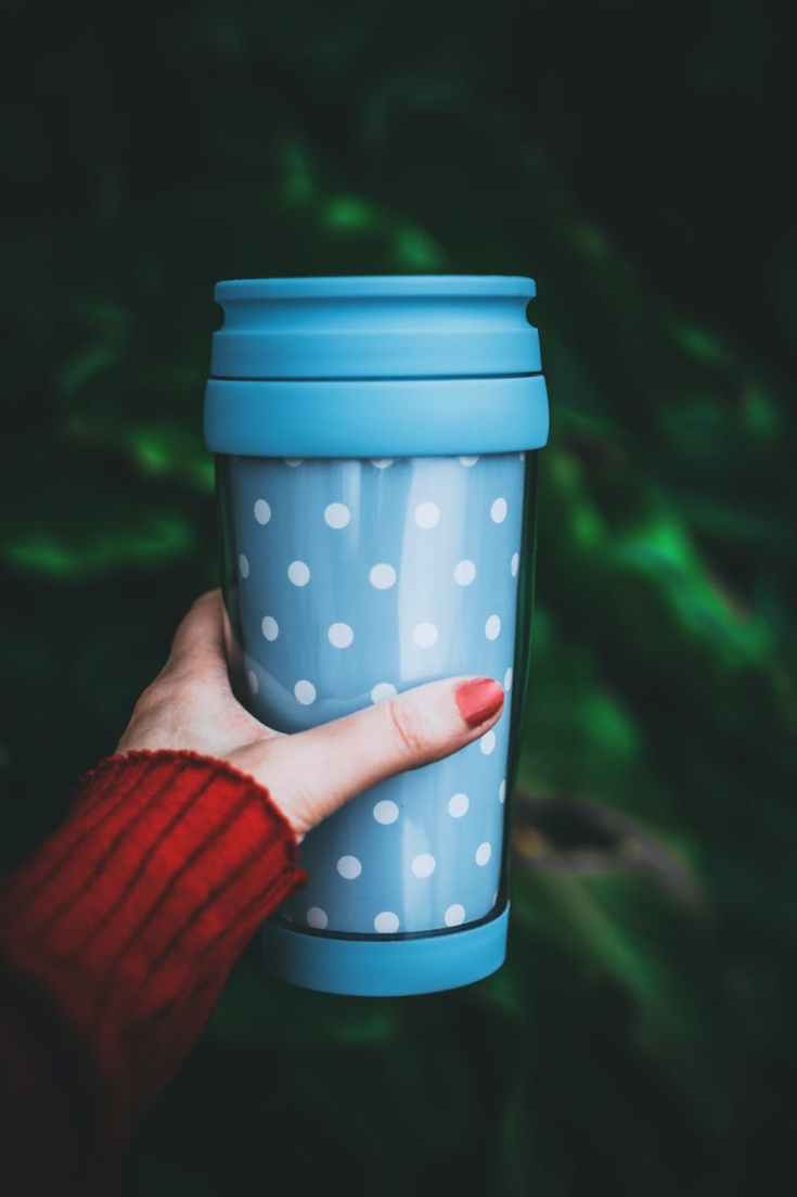 person holding teal and white polka dot tumbler
