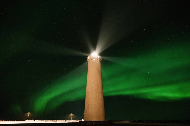 lighthouse against majestic green polar lights