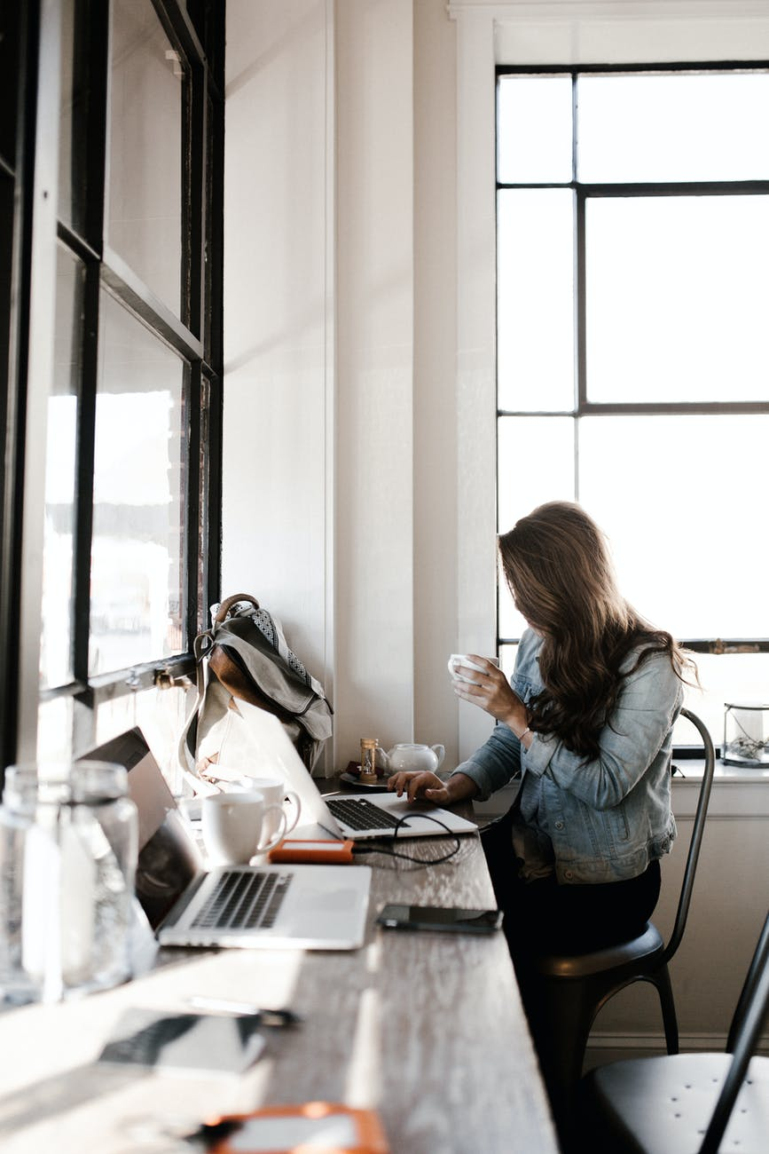 woman in gray jacket sitting beside desk