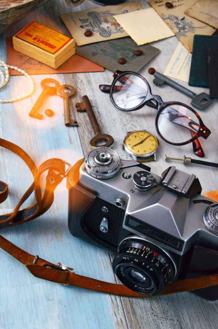 black and gray camera skeleton keys and brown framed eyeglasses on gray surface