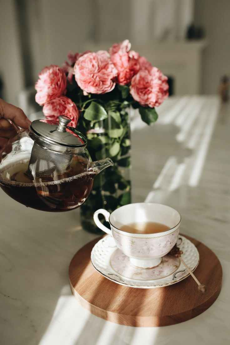 anonymous person pouring tea in cup near roses